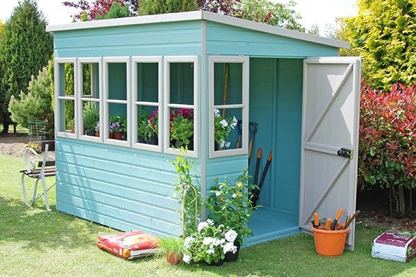 a blue and white potting shed with a pent roof