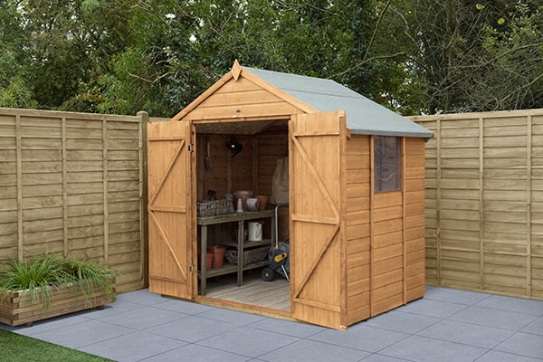 wooden double door shed with doors open sitting on a grey patio with fencing and trees behind