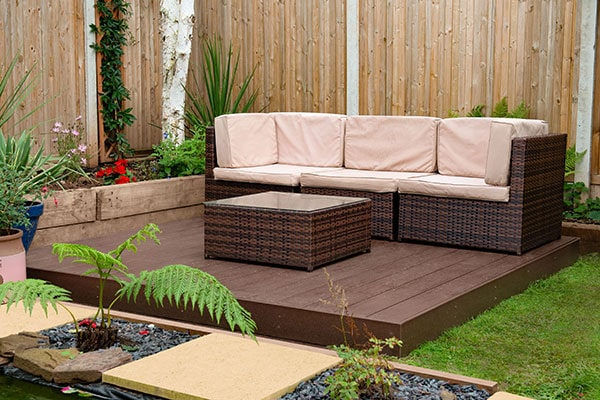a garden sofa and stool on top of a brown composite deck kit