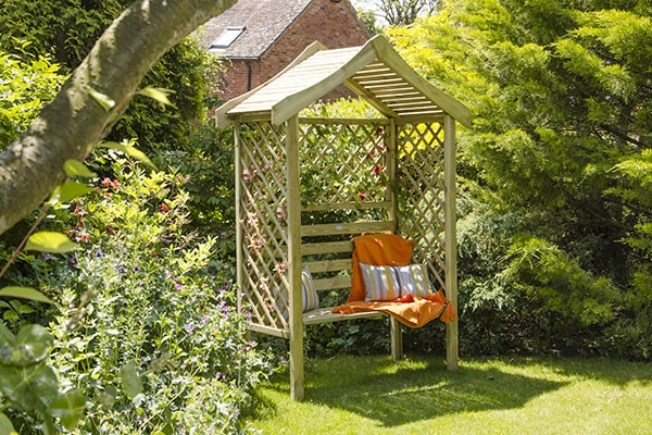 a pretty wooden arbour in a sunny garden with cushions and a blanket