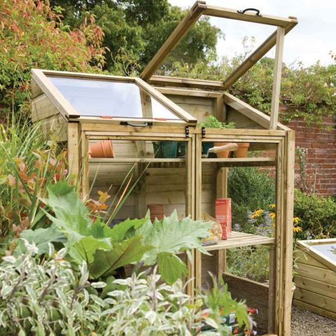a wooden mini greenhouse in situ containing potted plants and gardening sundries