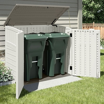 The 4x3 Suncast Resin Kensington Plastic Bin Store, situated on a lawn, with doors and lid open, and 2 green wheelie bins inside.