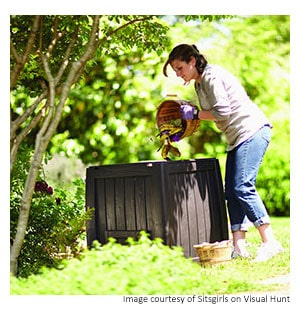 a woman adding garden waste to a composter