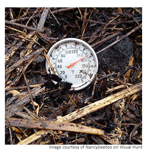 a thermometer in a full compost bin