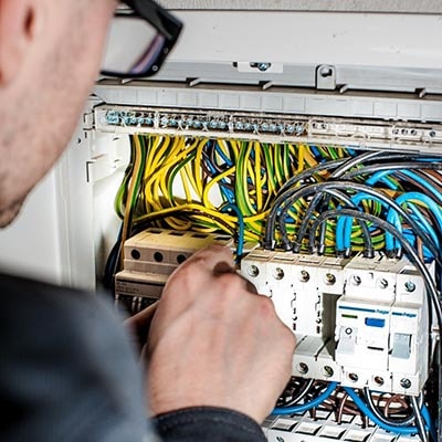 An electrician working on a fusebox